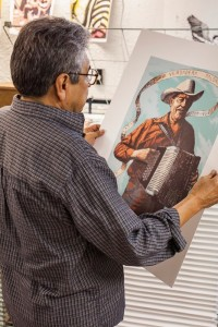 Sam Coronado checking out Serie XIX artist, Rigoberto Gonzalez's print. 2012